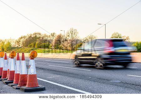 Evening view UK Motorway Traffic Roadworks Cones.