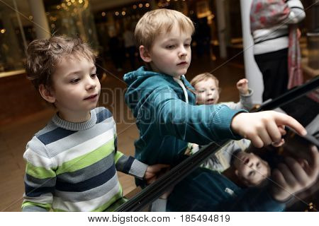 Brothers playing with touch screen in a museum