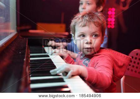 Children playing on light music piano at playground