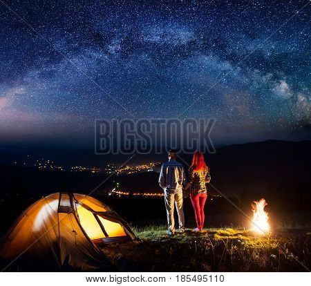 Night Camping. Happy Couple Hikers Holding Hands, Standing Near Camping And Enjoying Starry Sky. Lum