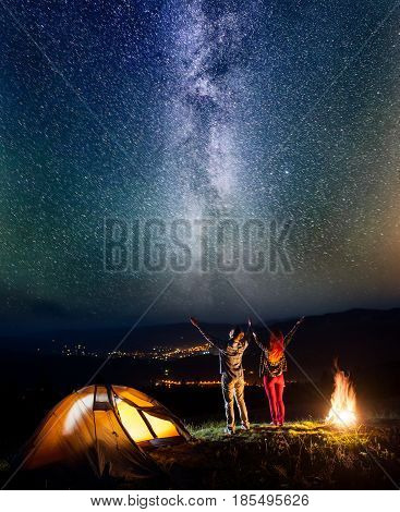 Romantic Couple Backpackers Raised Their Hands Up Under The Stars Near Bonfire And Tent, Looking On