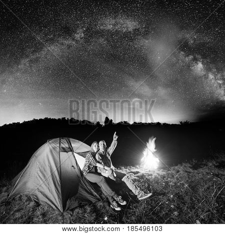 Night Tent Camping. Pair Sitting Near Tent And Campfire And Enjoying Incredibly Beautiful Starry Sky