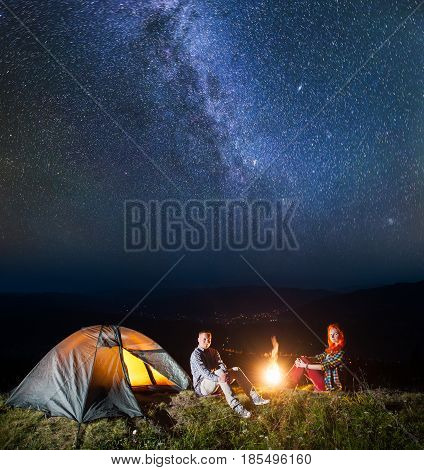 Tourist Family - Man And Woman Sitting By Bonfire Under Incredibly Beautiful Starry Sky At Night. On