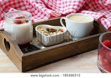 Wooden tray with fruit on the bottom yogurt jar muesli and cup of coffee. Healthy breakfast.