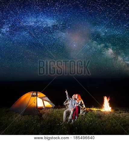 Guy Showing Red-haired Girl At The Stars And Milky Way In The Sky. Couple Sitting Near The Glowing T