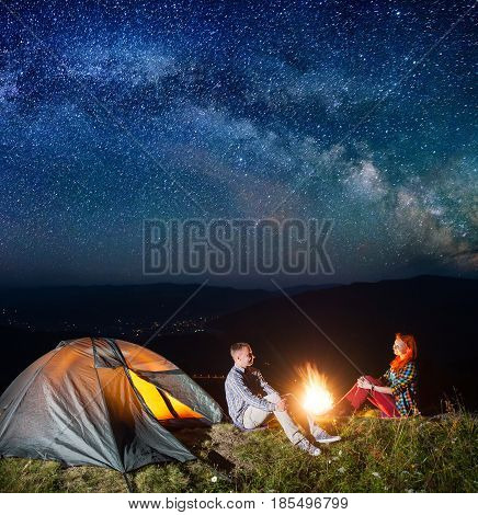 Night Camping. Young Couple Tourists Sitting By Campfire And Tent Under Incredibly Starry Sky. Lumin
