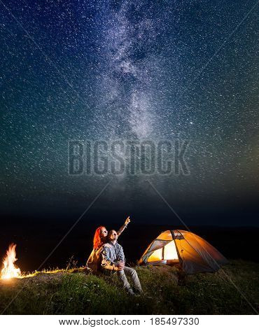 Two Lovers - Girl And Guy Looking At The Shines Starry Sky At Night. Loving Couple Sitting Near Tent