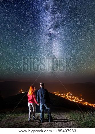 Tourist Family - Man And Woman Holding Hands, Standing On A Hill And Enjoying Amazing Starry Sky, Mi