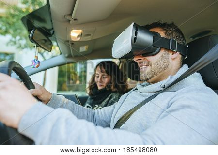 Driving instructor teaching a student using virtual reality glasses.