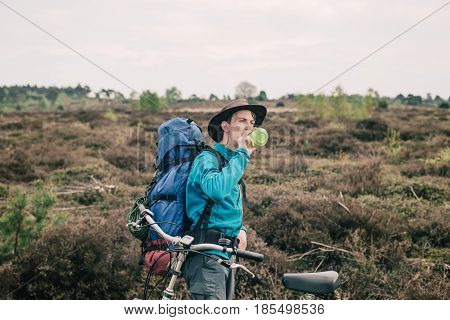 Nomad Standing Next To Bicycle In Moorland Drinking From Bottle.