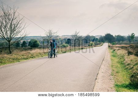 Tourist With Backpack Walking With Bicycle On Road In Moorland.