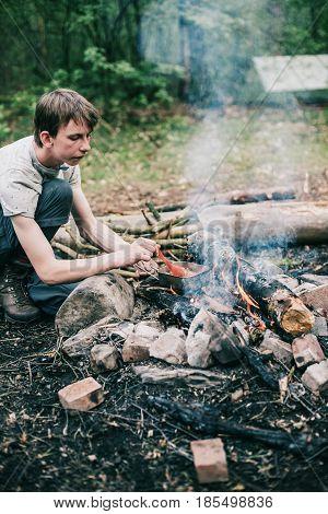 Wayfarer Stirring Meal In Frying Pan On Campfire.