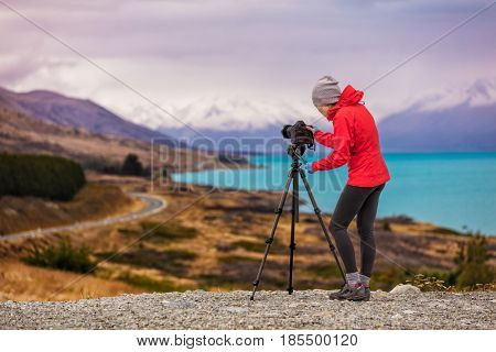 Photographer taking New Zealand travel nature photography. Woman photographer shooting with tripod and slr camera in sunset with beautiful landscape in background.