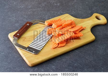 Yams, sweet potato cut in pieces with a special knife with ribs on a cutting board on a grey background. Cooking step by step. Home cooking, Healthy eating concept