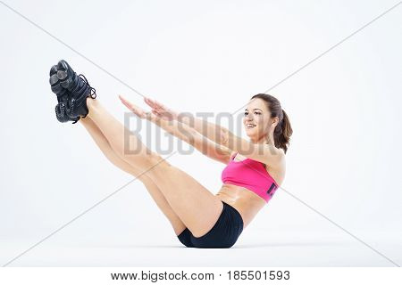 Young attractive slender girl performs sports exercises. Female model is engaged in sports on a white background, isolate. Healthy life and sport. Cute girl performs a handstand - Plank exercise.