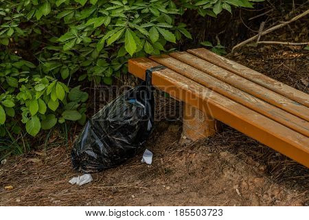Black trash bag full of trash tied to a wooden park bench in woodland area of South Korea