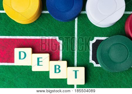 Gambling addiction abstract concept. Debt made out of letter tiles.