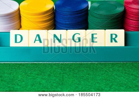 Gambling addiction abstract concept. Danger made out of letter tiles.