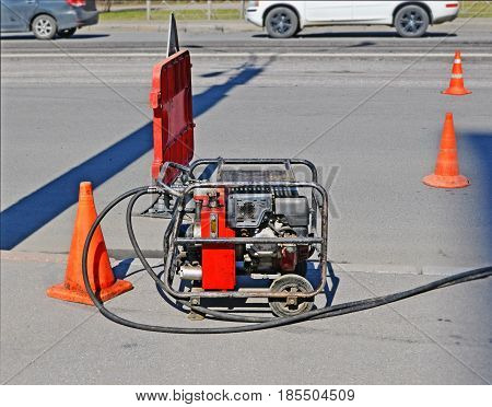 Industrial compressor on road during repairs. Site is fenced with warning road sign and signal cones.