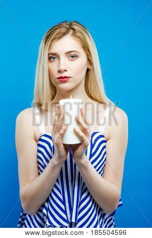 Pretty Blonde with Bare Shoulders Wearing Striped Dress is Holding White Candle in Her Hands on Blue Background. Portrait of Serious Girl in Studio.