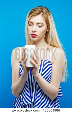Beautiful Blonde with Bare Shoulders Wearing Striped Dress is Holding Candle in Her Hands and Looking on it. Portrait of Sad Serious Girl on Blue Background in Studio.