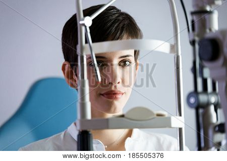 Optometrist examining patient in ophthalmology clinic with professional equipment