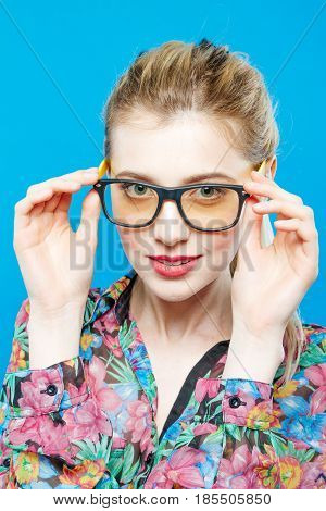 Joyous Girl in Eyeglasses is Posing in Studio Looking at the Camera. Portrait of Blonde Woman with Ponytail Wearing Colorful Shirt on Blue Background.
