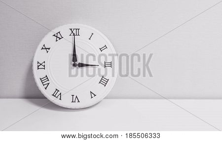 Closeup white clock for decorate in 3 o'clock on white wood desk and wallpaper textured background in black and white tone with copy space