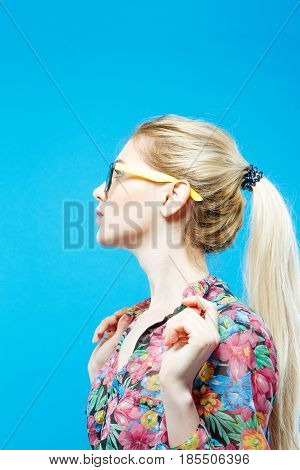 Side View of Cute Girl with Ponytail Wearing Colorful Shirt and Eyeglasses on Blue Background in Studio.