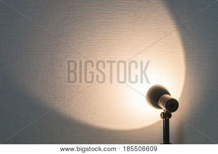 Closeup wallpaper wall textured background with blurred small lamp with brown light shine to the wall with copy space