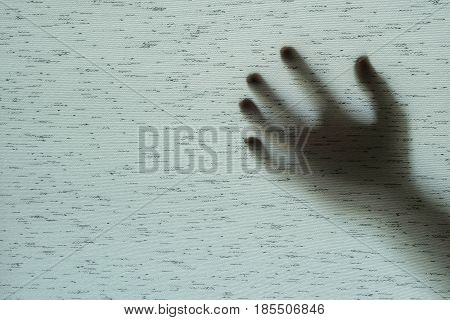 Closeup surface shadow of hand behind gray fabric curtain textured background with copy space in horror concept