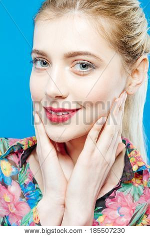 Portrait of Beautiful Blonde Woman with Ponytail and Perfect Skin Wearing Colorful Shirt on Blue Background. Smiling Girl is Posing in Studio Looking at the Camera.