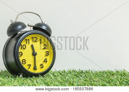 Closeup black and yellow alarm clock for decorate show half past eleven o'clock or 11:30 a.m. on green artificial grass floor and cream wallpaper textured background with copy space