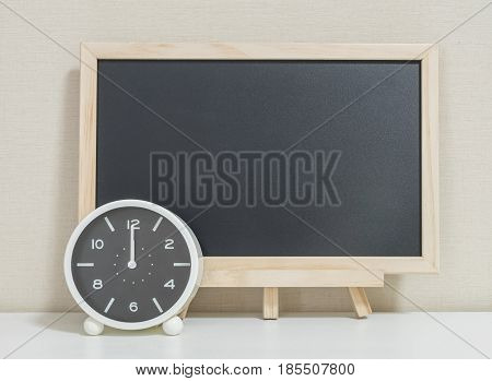 Closeup alarm clock for decorate show 12 o'clock with wood black board on white wood desk and cream wallpaper textured background selective focus at the clock