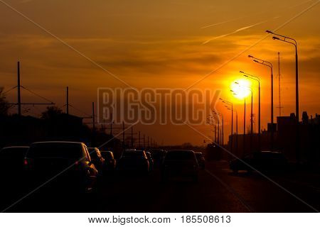 Car traffic against the sunset background - modern city - silhouette, horizontal