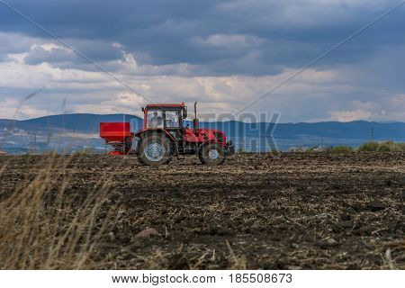 Tractor spreading artificial fertilizers in spring days