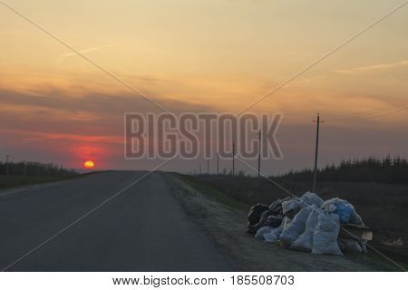 Garbage dump along the road at sunset - ecology concept, horizontal