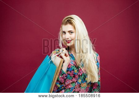 Blonde Female Shopper Wearing Colorful Shirt is Holding Shopping Bags in Studio. Happy Girl with Lond Hair and Charming Smile on Pink Background.