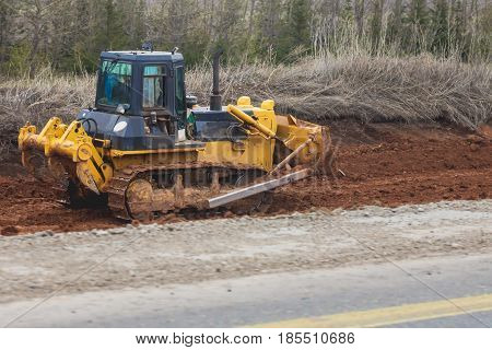 Road machinery - yellow excavator on a road construction site, telephoto