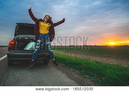 Teenage girl jumping on open road near car on sunrice