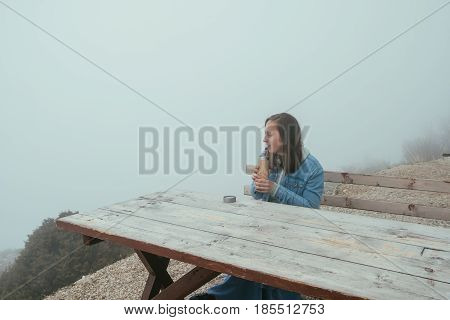 Young Woman Sitting On Wooden Bench And Drinking Hot Tea From A Thermos In Autumn Forest.