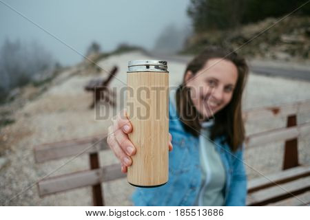 Closeup Woman Hand With Thermos In Autumn Forest.