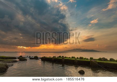 A view of Nha Trang bay just before sunrise with a moss covered jetty in the foreground.