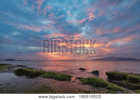 A view of Nha Trang bay just before sunrise with moss covered rocks in the foreground.