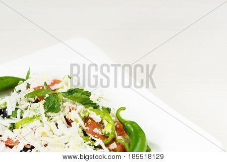Traditional classic Shopska salad with tomatoes, peppers, cucumbers and cheese in white dish on white wooden table. Bulgarian cuisine, Balkan culture