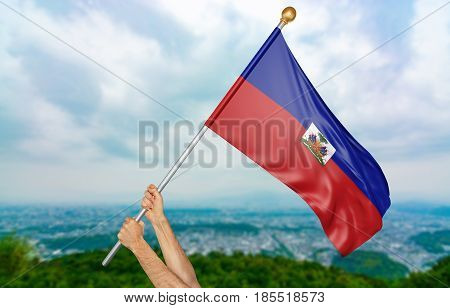 Young man's hands proudly waving the Haiti national flag in the sky, part 3D rendering