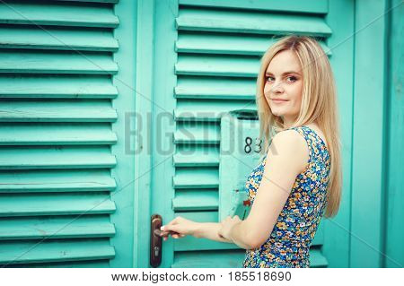 Smiling young woman in dress with arms crossed standing against blue wood wall.