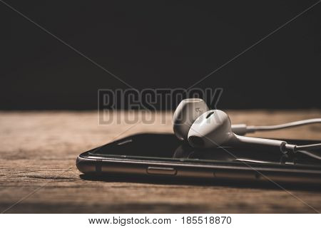 Earphone and phone media portable on dark tone. Earphone and smartphone. Earphone and smartphone vintage tone. Earphone and smartphone music. Earphone and smartphone concept