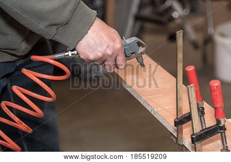 Worker Cleaning Furniture Panel Surface, With Compressed Air