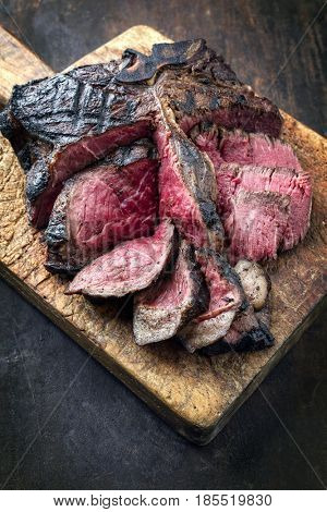 Barbecue dry aged Wagyu Porterhouse Steak as close-up on an old cutting board